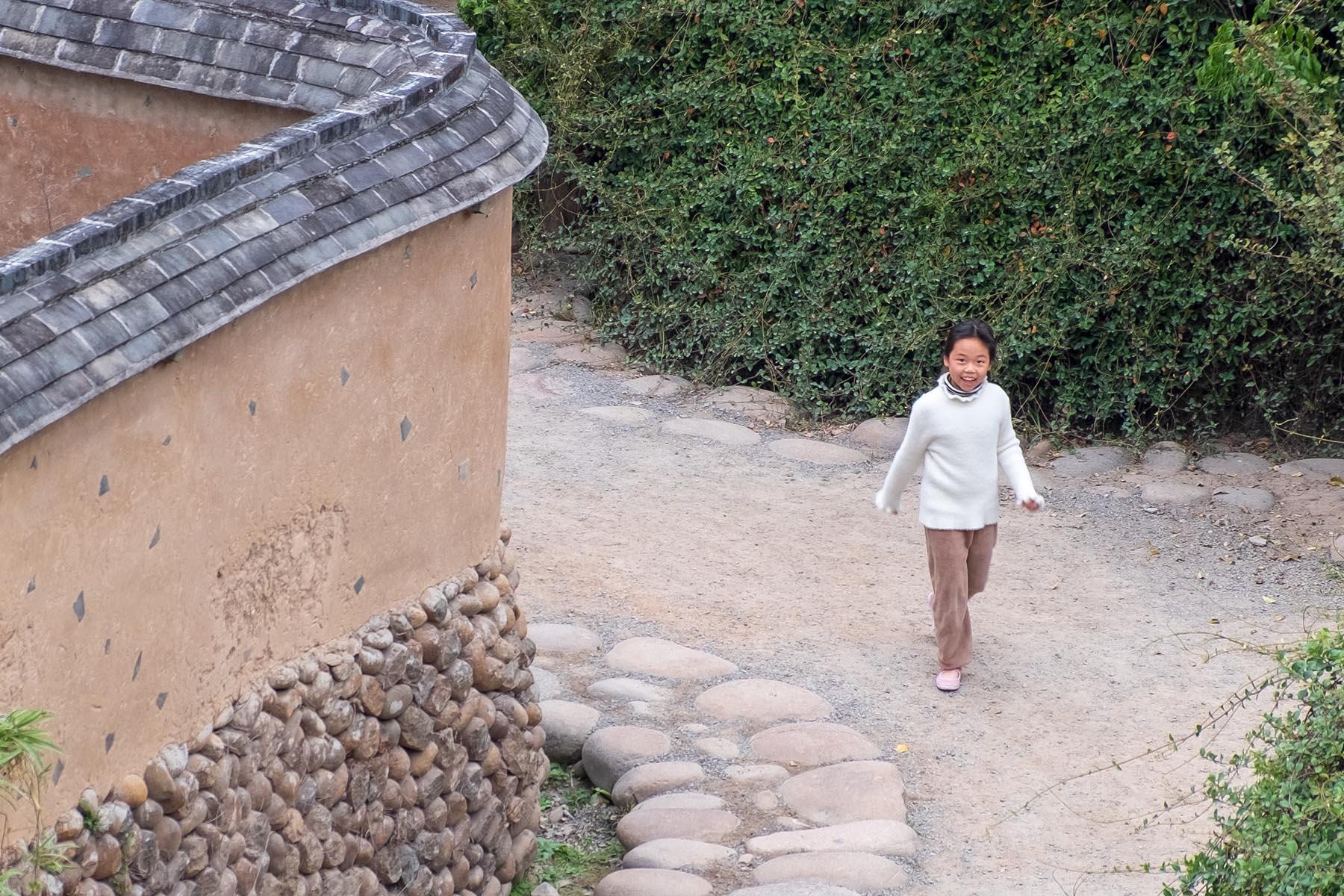 Ein Mädchen aus Songkou in Fujian, China lacht in die Kamera