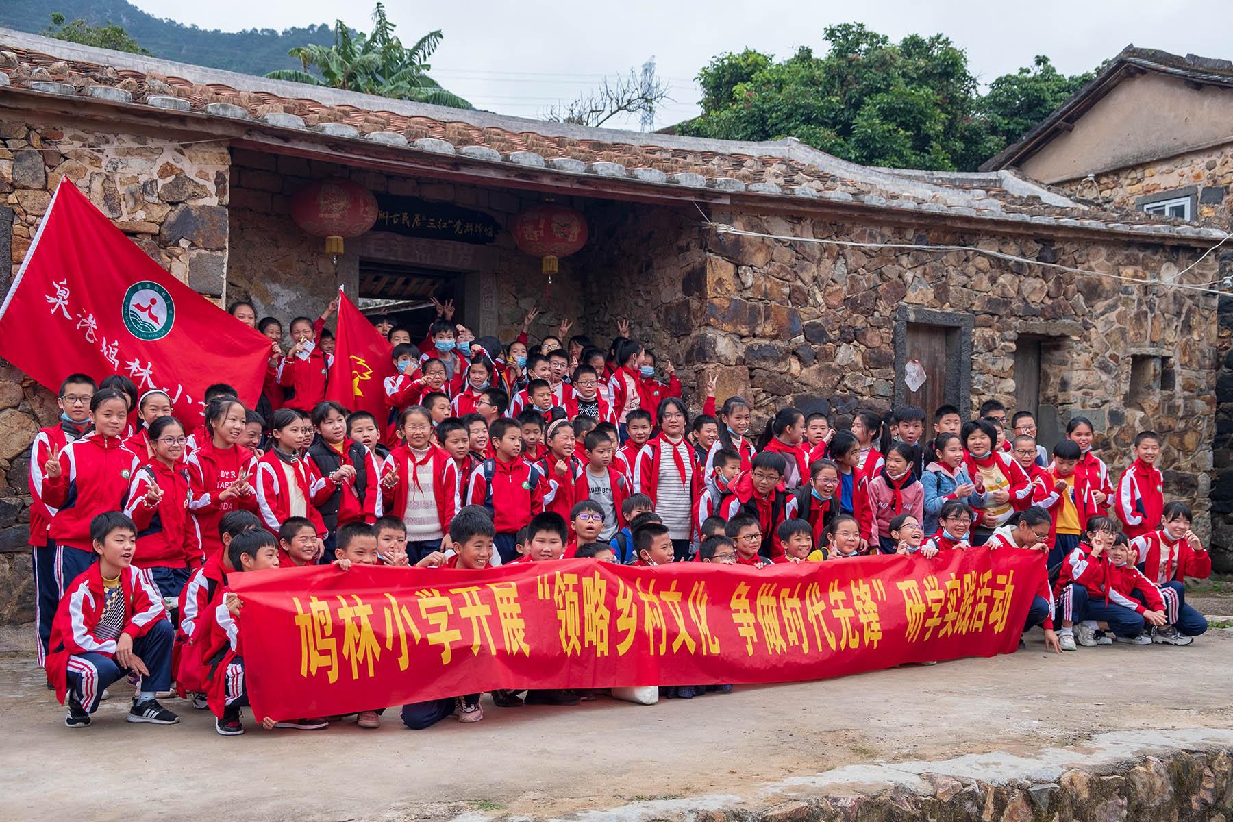 Schüler vor Steinhaus in Zhangjiao in der Provinz Fujian, China