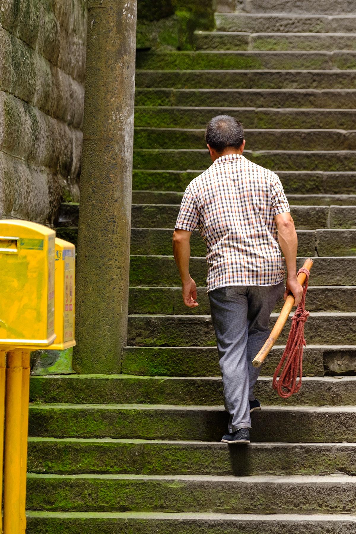 Ein Mann läuft die Treppe hinauf in Chongqing