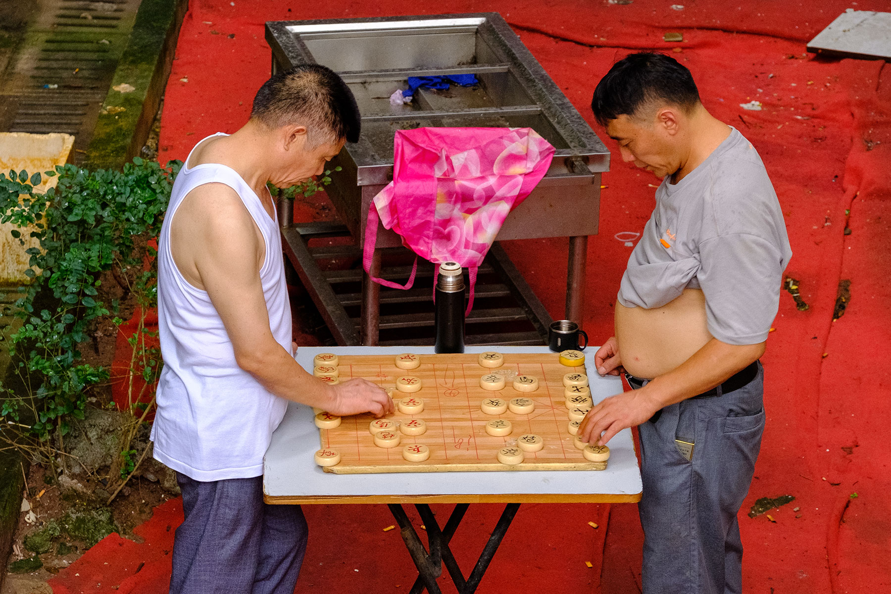 Männer spielen Brettspiel an einem heißen Sommer Tag in Chongqing in China