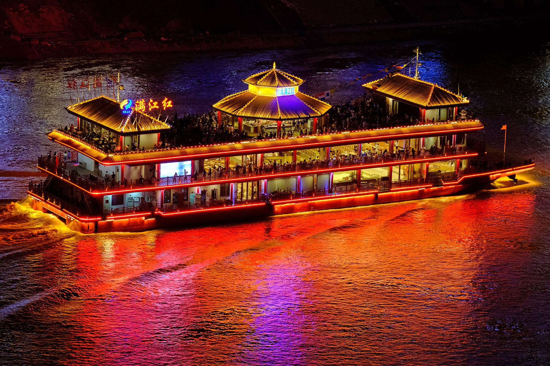 Beleuchtetes Boot auf Fluß bei Nacht in Chongqing