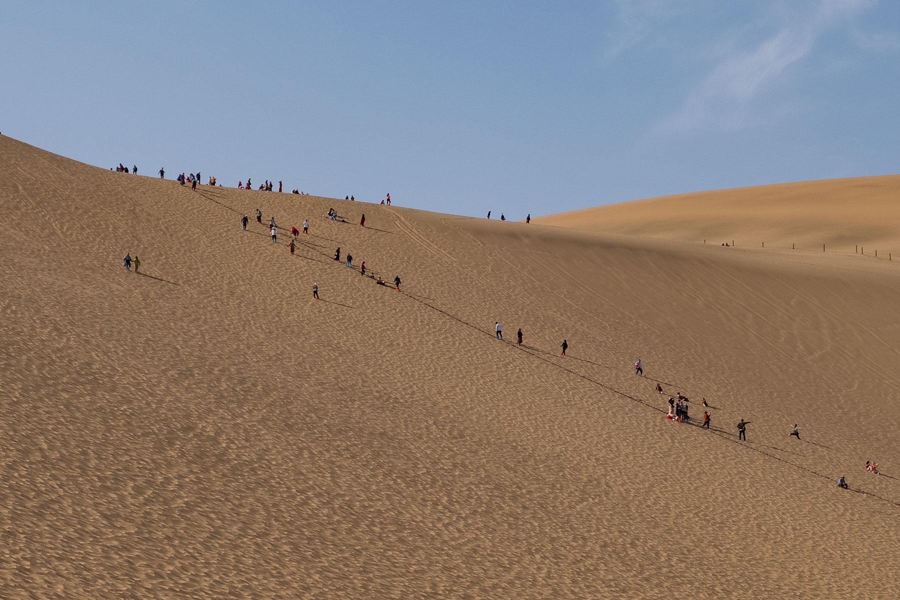 Menschen im Sand in der Mingsha Wüste in Dunhuang in China