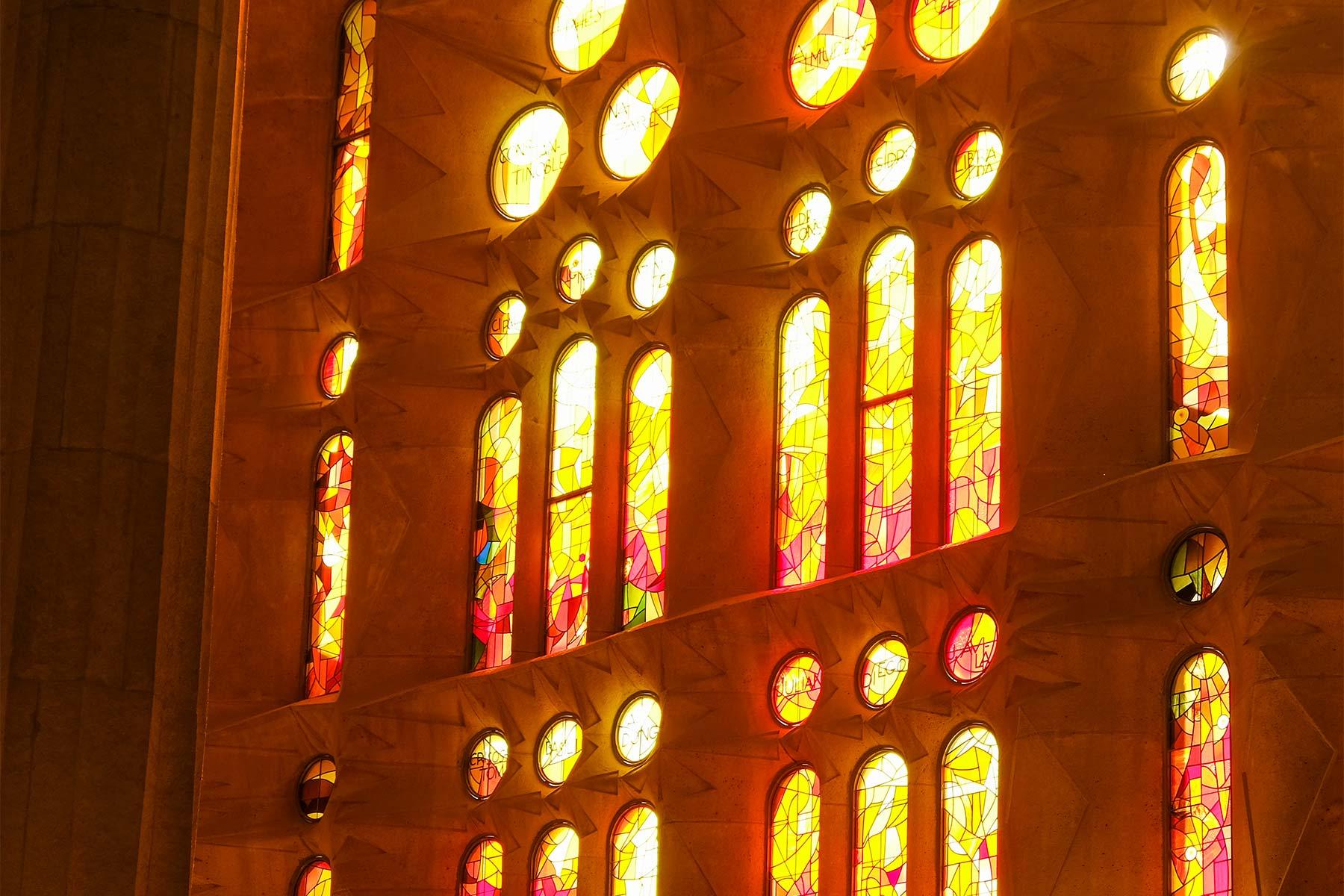 In Rot, Orange und Gelb gehaltene Glasscheiben auf der Passionsseite der Sagrada Familia