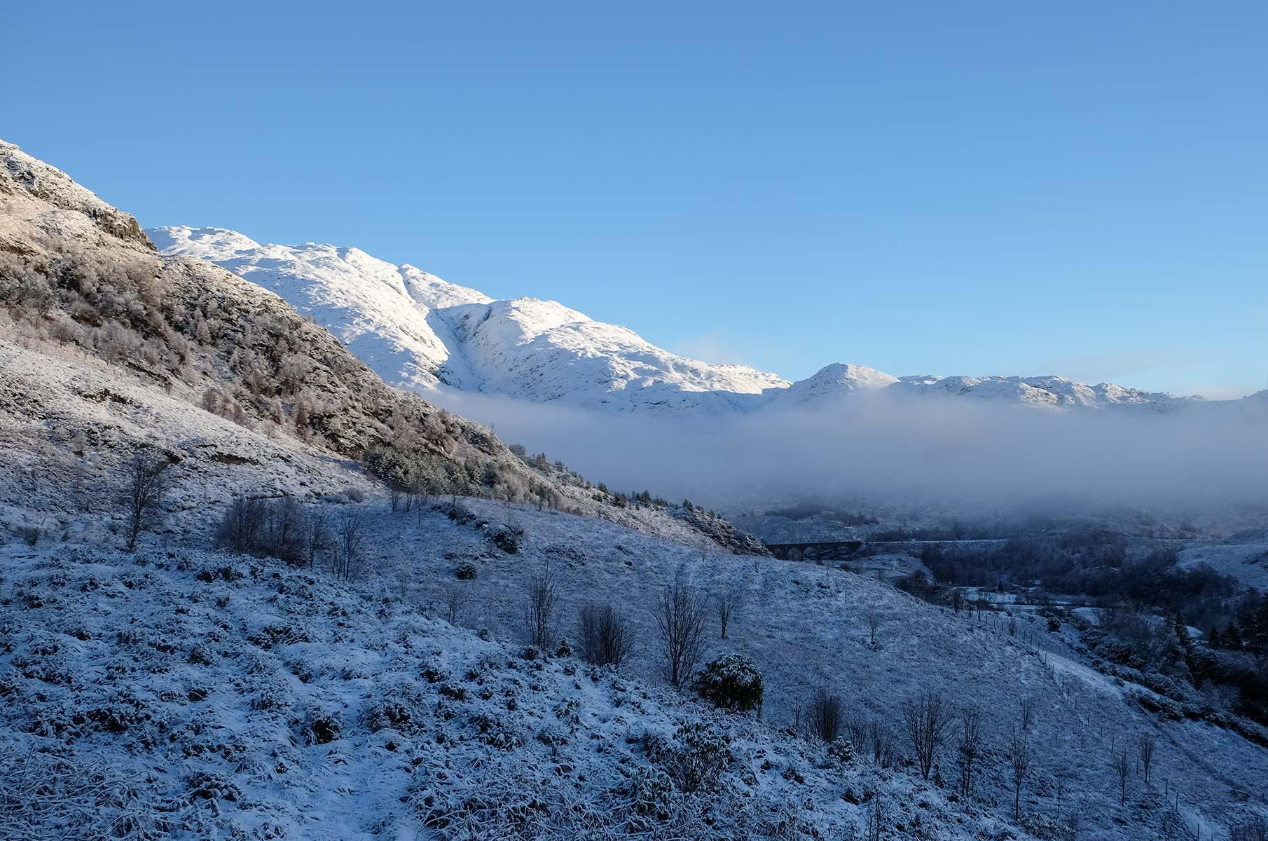 Blick auf eine Winterlandschaft und das Glenfinnan Viadukt in Schottland