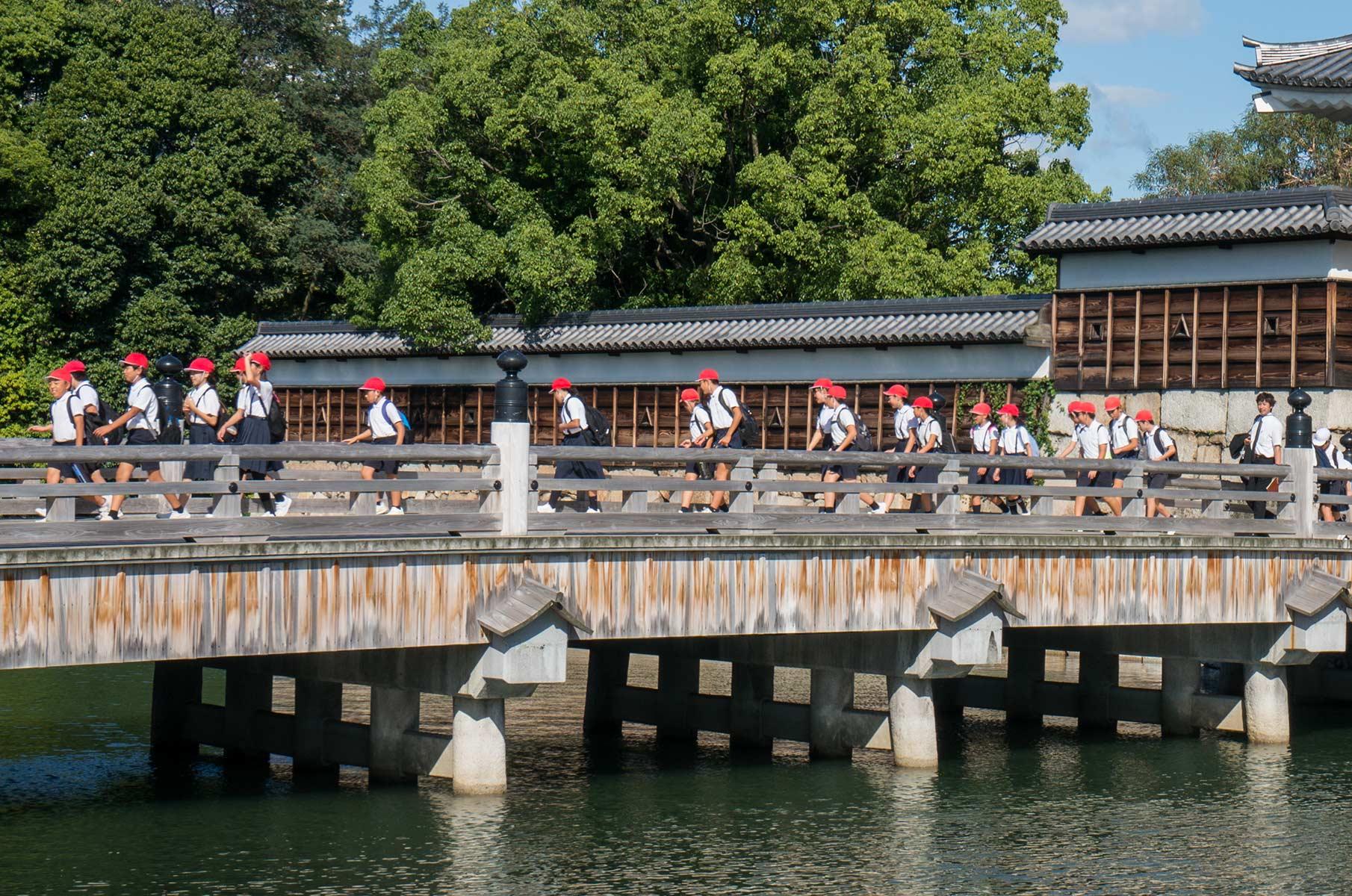 Japanische Schüler auf einer Brücke auf der Burg Hiroshima in Japan