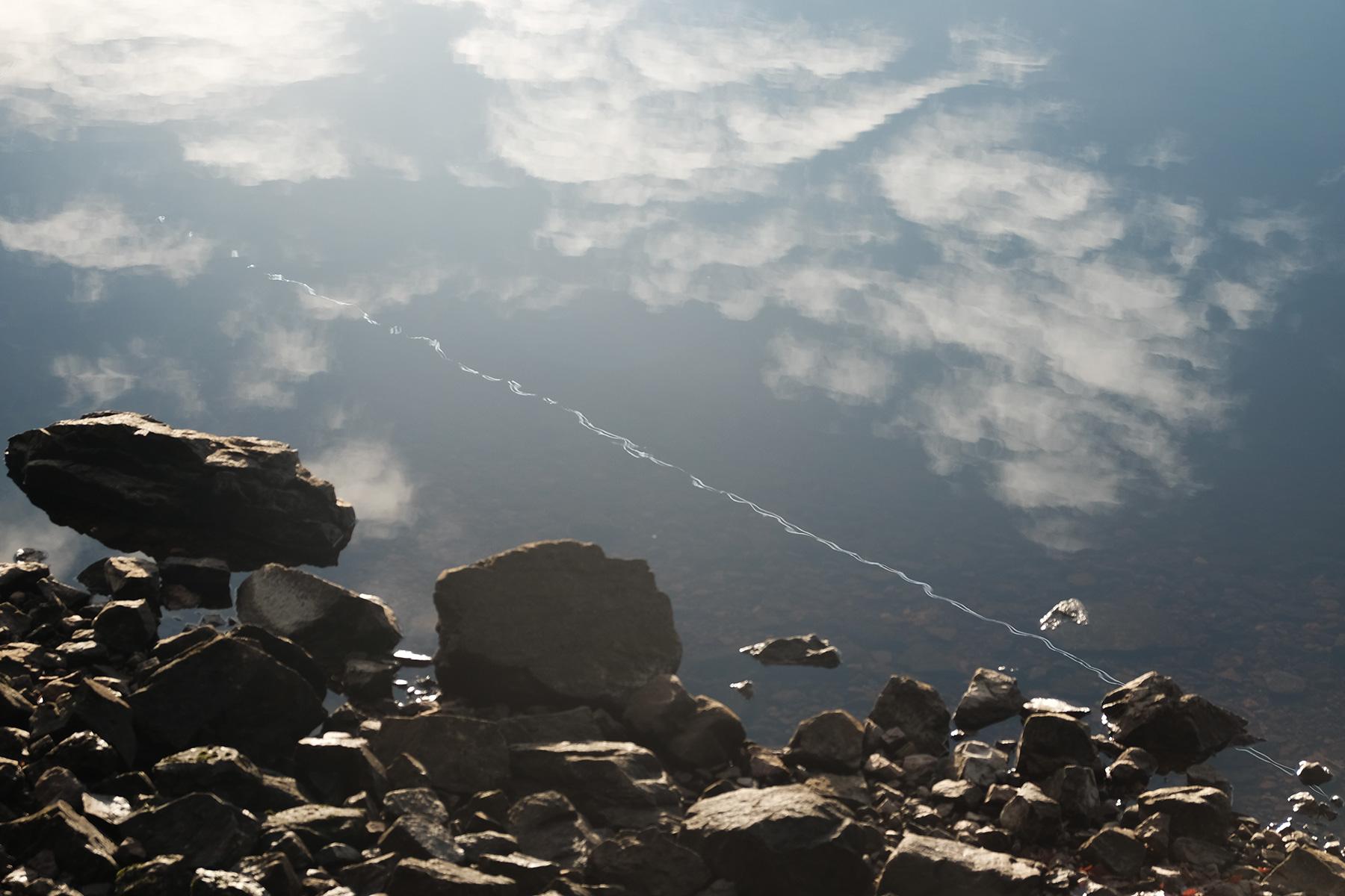 Spiegelung des Himmels und eines Flugzeugkondensstreifens im Loch Garr in Schottland