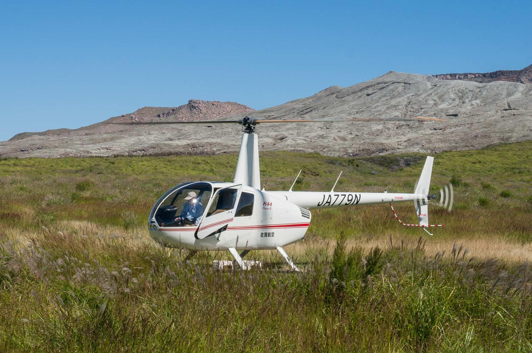 Robinson R44 Raven II Hubschrauber in der Mt. Aso Gras- und Vulkanlandschaft, Japan