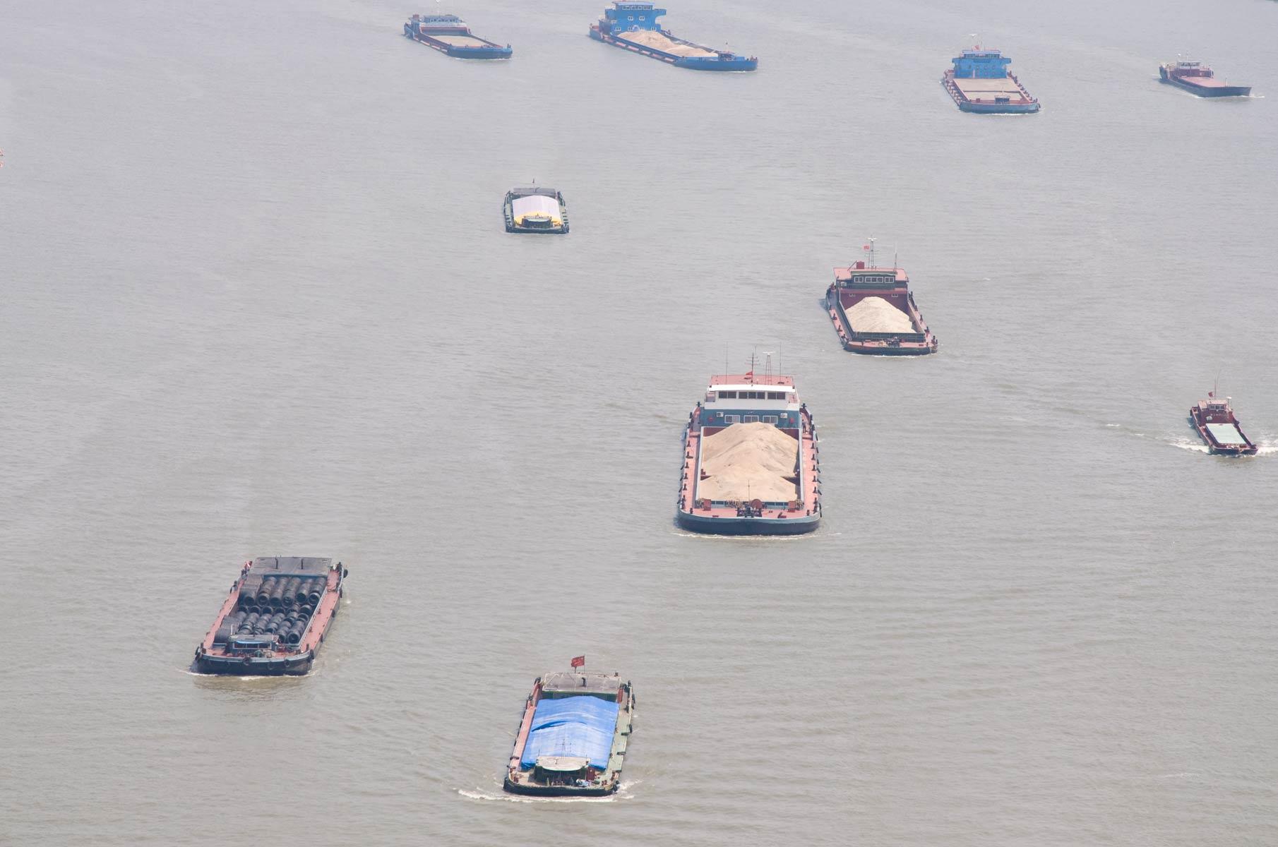 Blick von der Nanpu Brücke auf mehrere Schiffe auf dem Huangpu Fluss in Shanghai, China