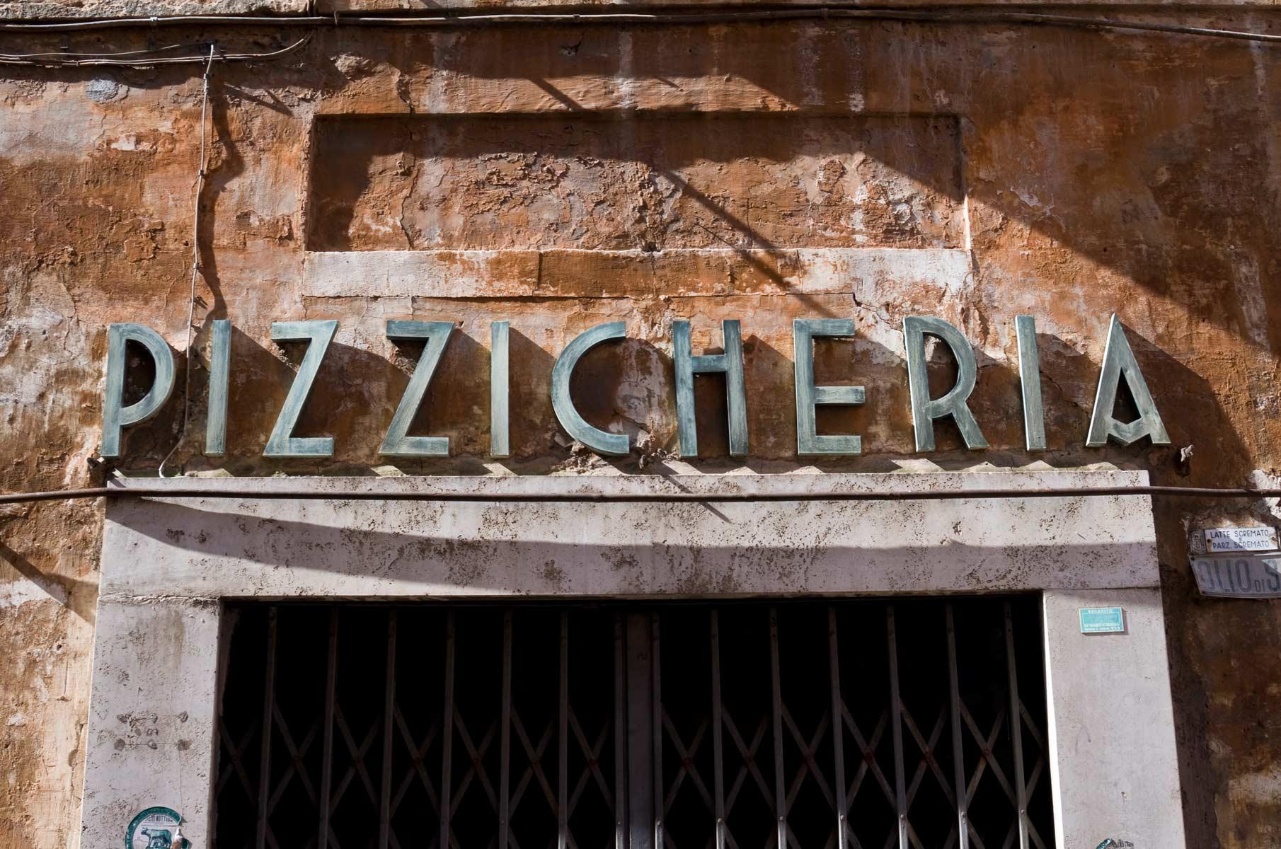 Straßenszene mit Pizzicheria Schild in Rom, Italien