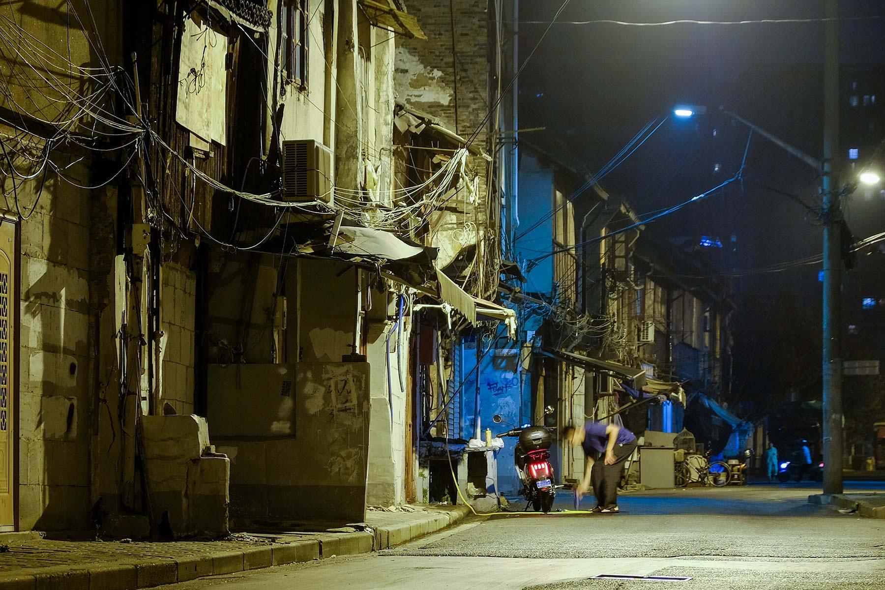 Shanghai Altstadt bei Nacht in der Gegend um Laoximen - Mann repariert Motorroller