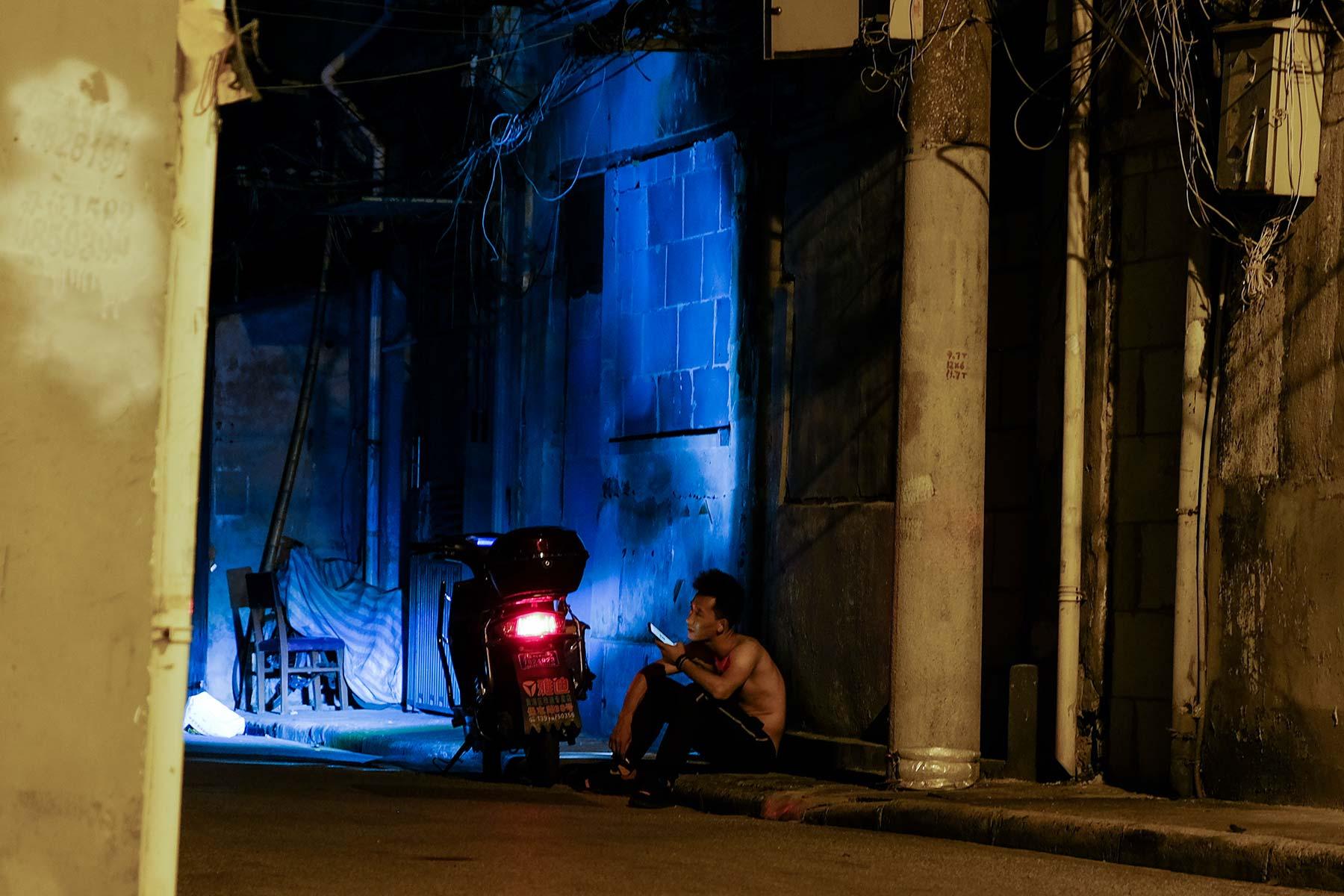 Mann sitzt neben Motorroller bei Nacht in Shanghai Altstadt