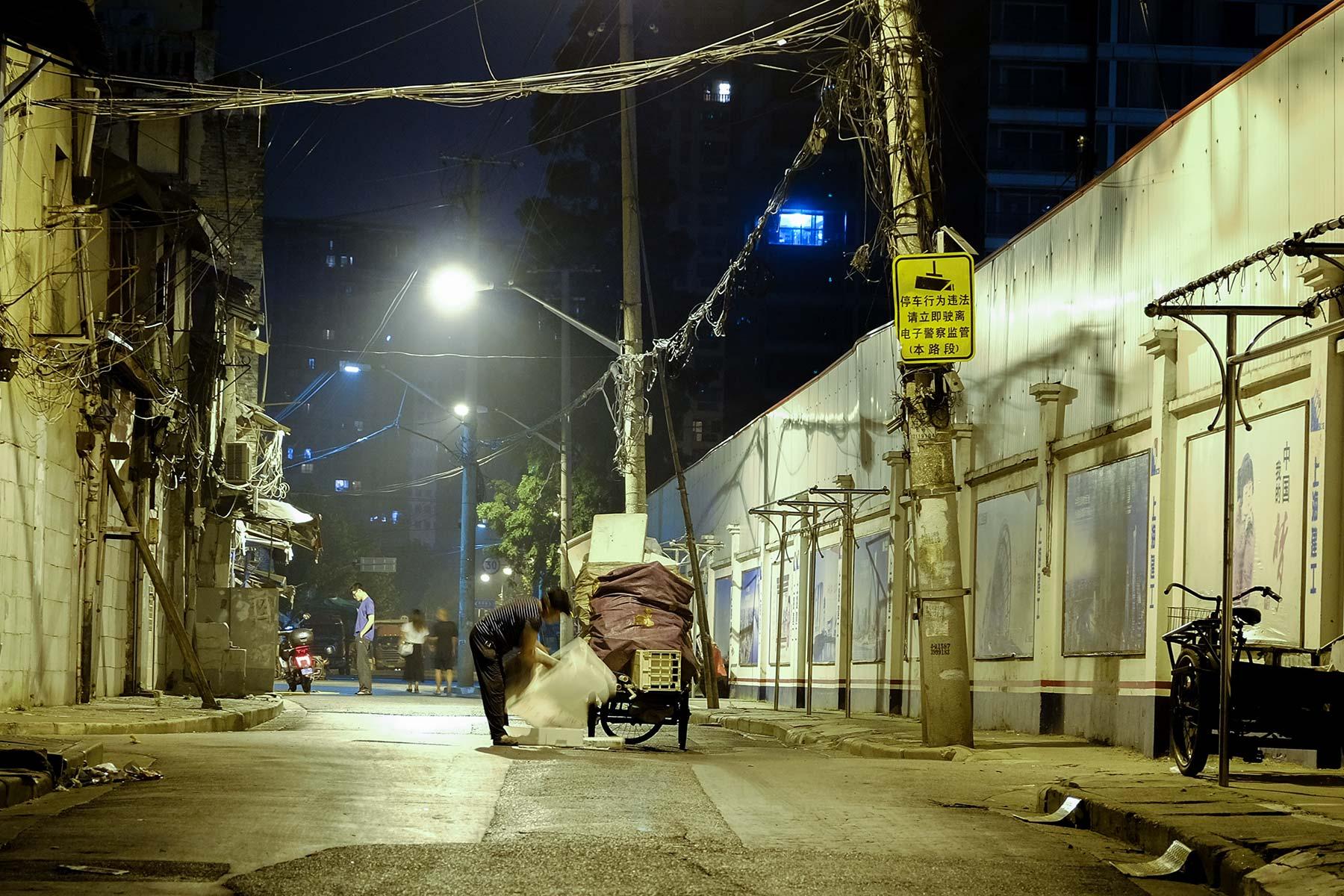 Frau sammelt Müll zum Recyclen bei Nacht in Shanghai Altstadt