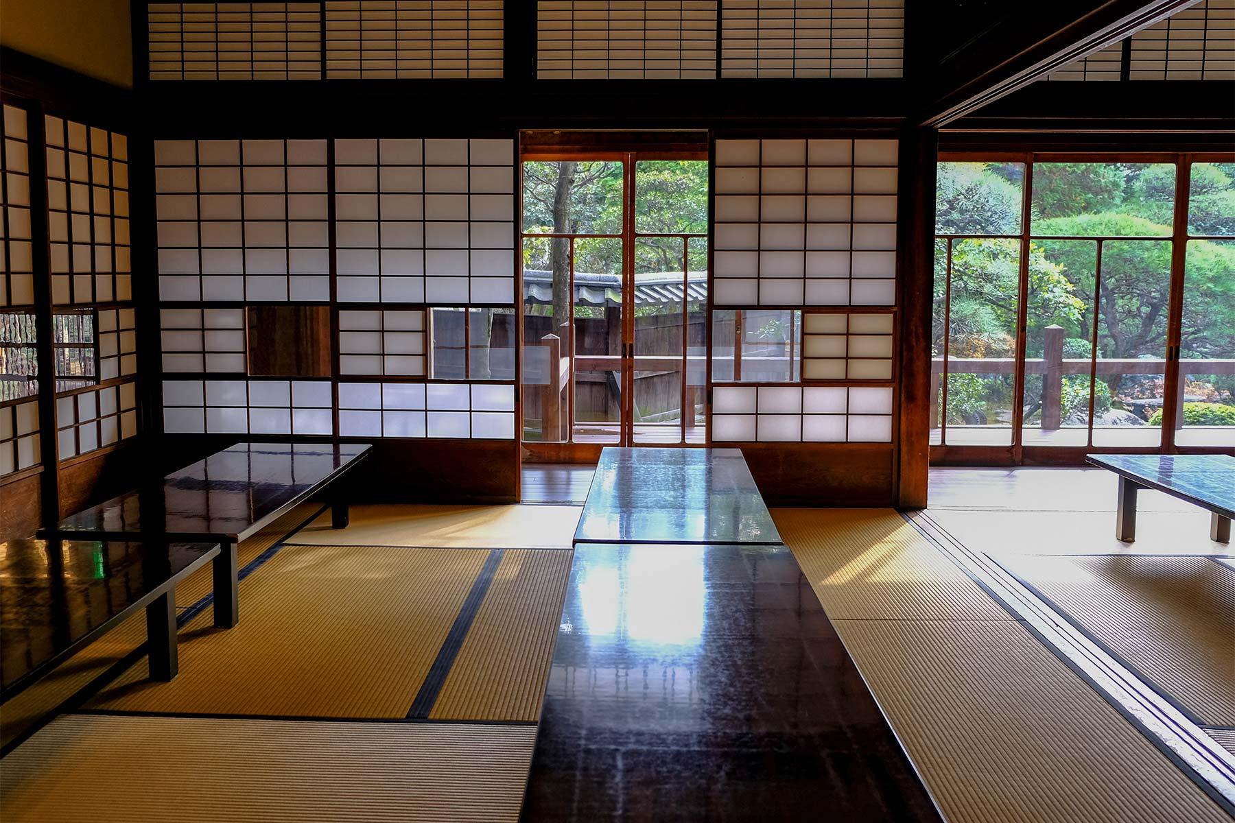 Wohnzimmer mit niedrigen Tischen, Tatami Böden und Blick in den Garten