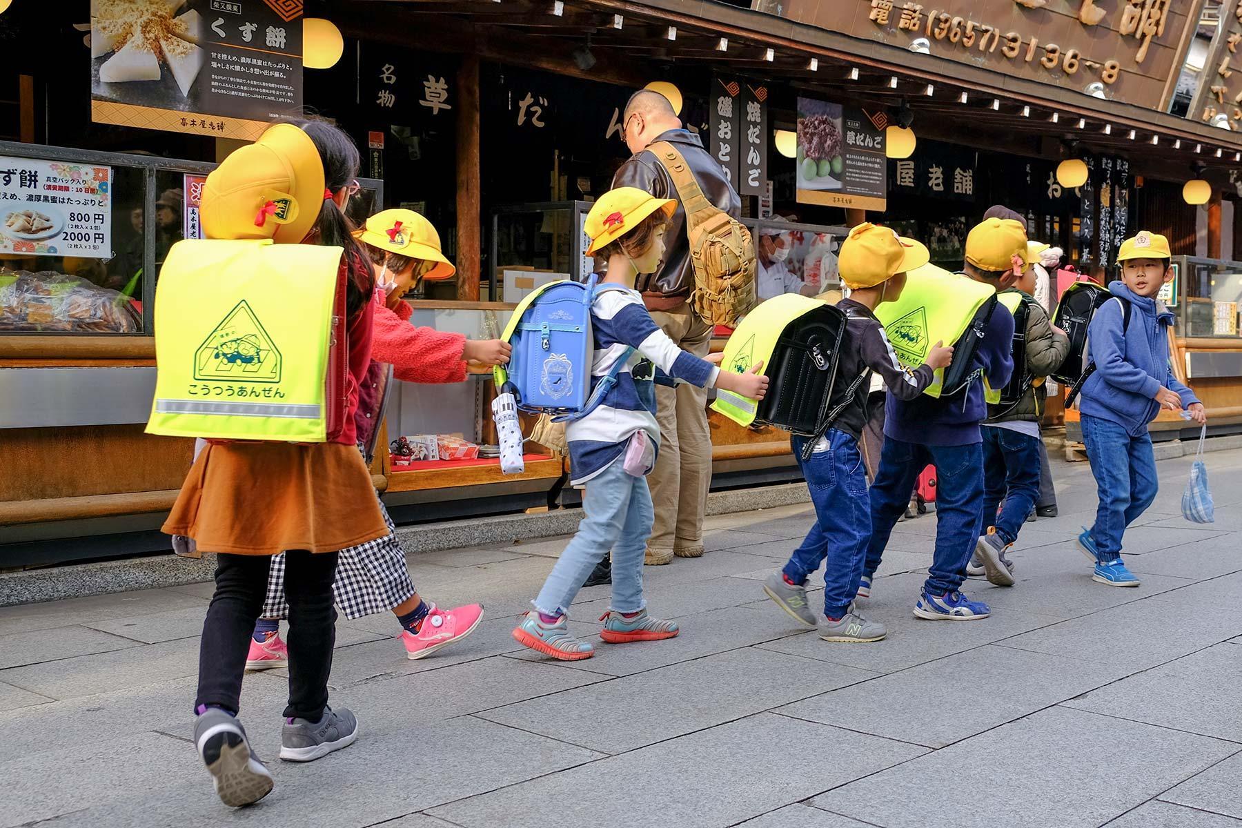 Grundschulkinder in Japan als 'Zug' unterwegs